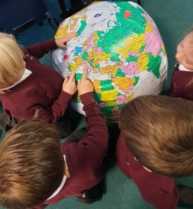 Pupils pointing to globe