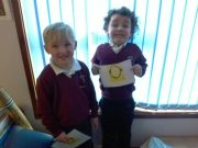 Early Years pupils with postcards for Aspiration and Respect